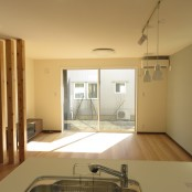 明るい日差しが入り込むリビングをキッチン側から見ています